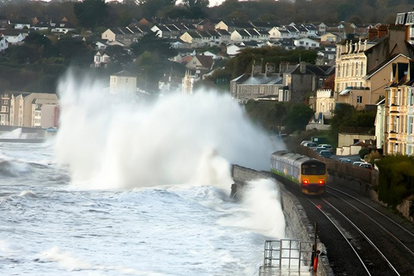 Dawlish train line by the sea with waves breaking