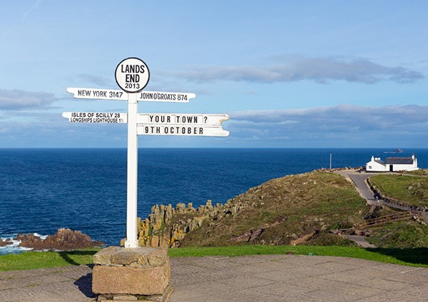 Sign posts for Lands End with see in background near Penzance