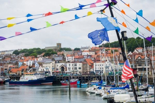 Scarborough harbour with flags on boats