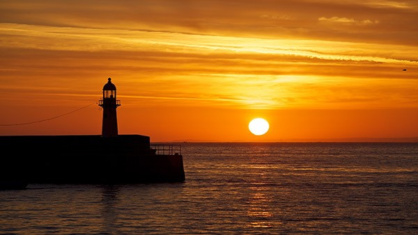 Sunrise at St Ives with lighhouse in foreground