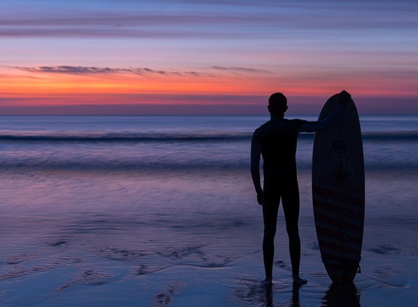 Surfer at sunrise on Fistral Beach in Newquay